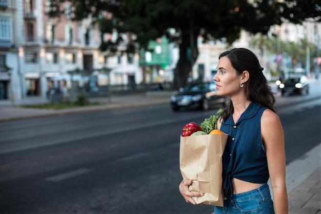 Mulher em tiro médio carregando um saco de papel