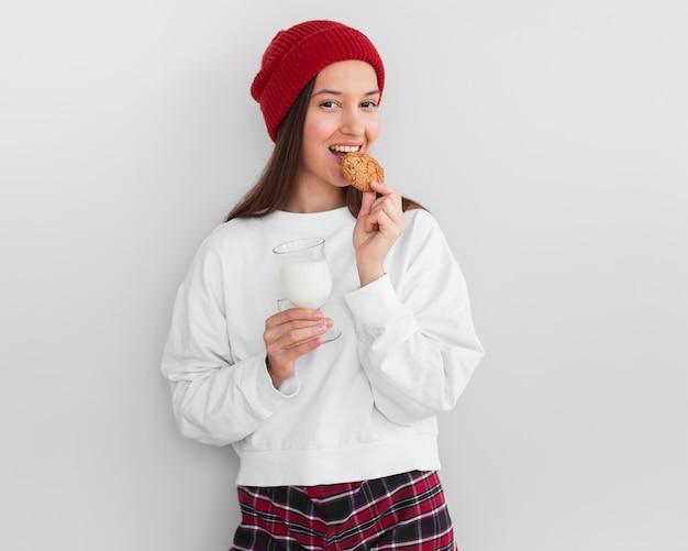 Mulher em tiro médio com chapéu comendo leite e biscoitos