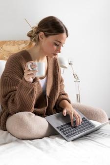 Mulher em tiro médio com laptop na cama
