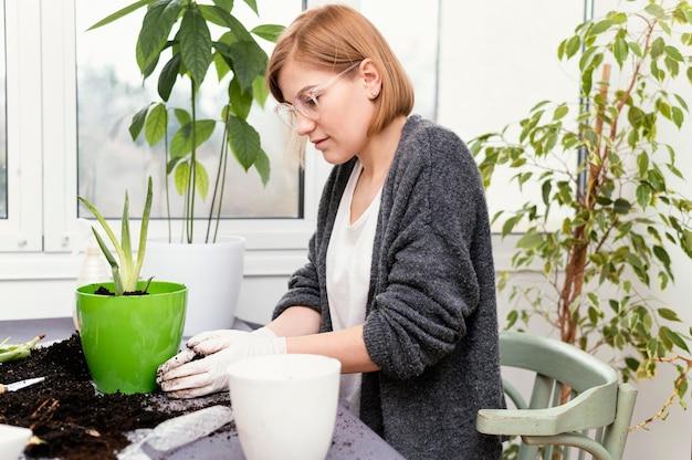Mulher em tiro médio com luvas de jardinagem
