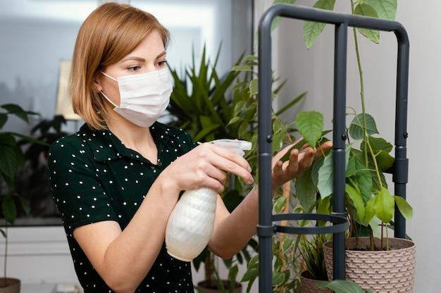 Mulher em tiro médio com máscara regando planta