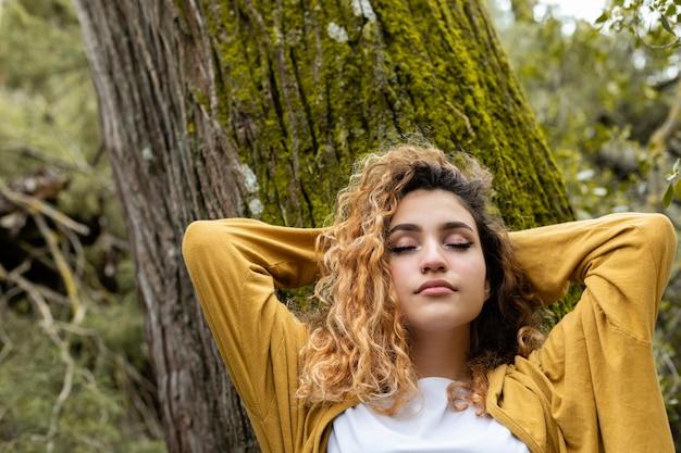 Mulher em tiro médio deitada em uma árvore