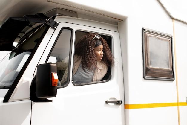 Mulher em tiro médio dirigindo um veículo