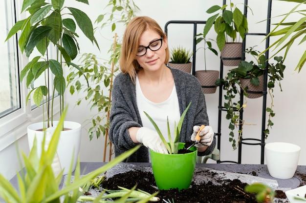 Mulher em tiro médio fazendo jardinagem com luvas