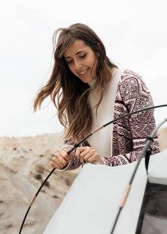 Mulher em tiro médio montando uma barraca
