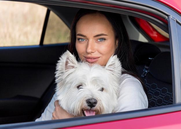 Mulher em tiro médio no carro com cachorro