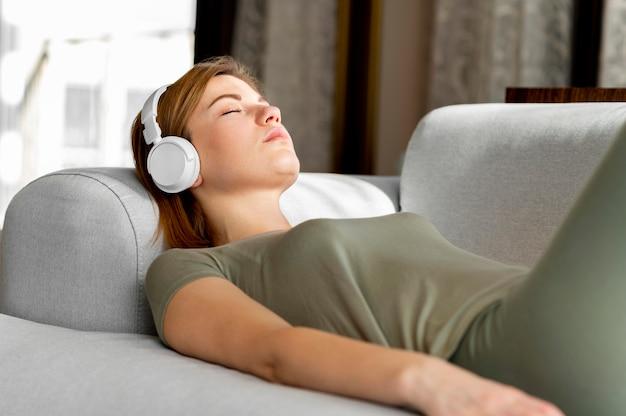 Mulher em tiro médio no sofá com fones de ouvido