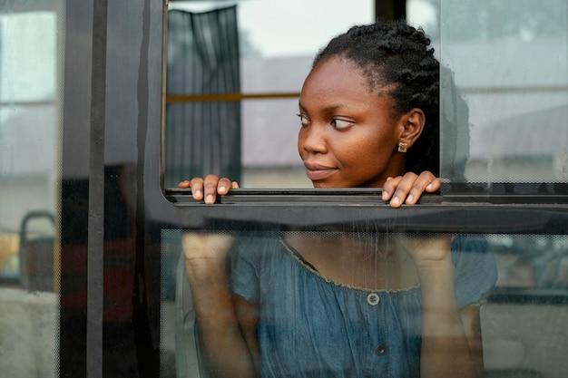 Mulher em tiro médio olhando pela janela