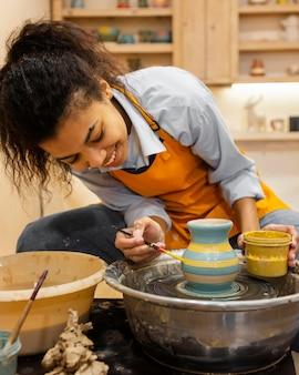 Mulher em tiro médio pintando panela de barro