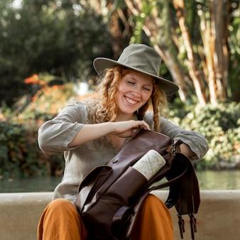 Mulher em tiro médio procurando na mochila