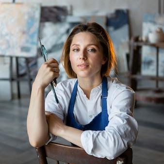 Mulher em tiro médio segurando ferramentas de pintura