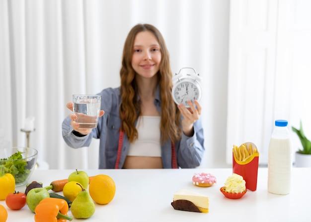 Mulher em tiro médio segurando um copo d'água