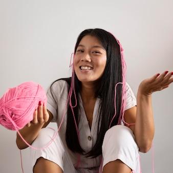 Mulher em tiro médio segurando um fio rosa