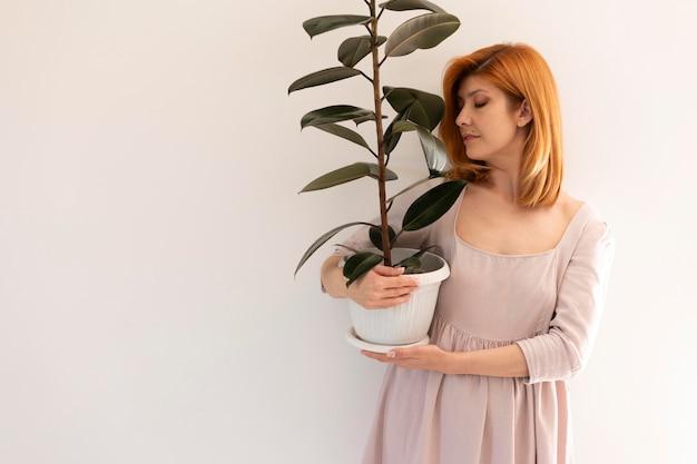 Mulher em tiro médio segurando um vaso de flores