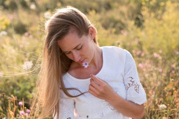 Mulher em tiro médio segurando uma flor roxa
