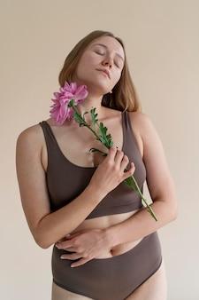 Mulher em tiro médio segurando uma flor
