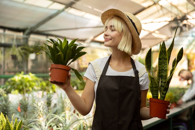 Mulher em tiro médio segurando vasos de plantas