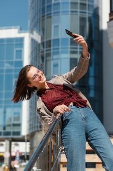 Mulher em tiro médio tirando uma selfie