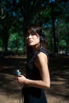 Mulher em tiro médio usando fones de ouvido Foto Premium