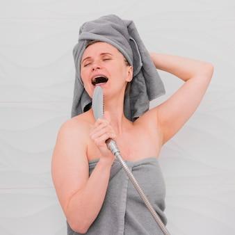 Mulher em toalhas cantando no banheiro