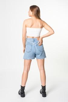 Mulher em top branco cai-cai e saia jeans, moda casual