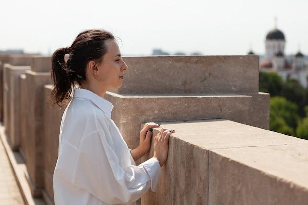 Mulher em toursit olhando para a cidade metropolitana do terraço panorâmico