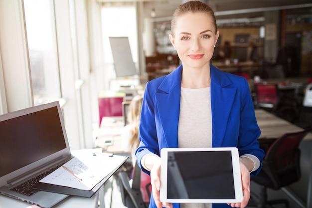 Mulher em traje azul, sorrindo para o escritório segurando o tablet