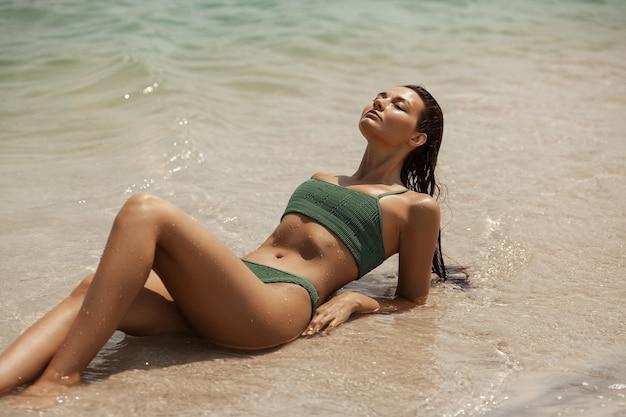 Mulher em traje de banho deitado em uma praia na água com os olhos fechados para o mar. garota deslumbrante em