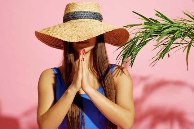 Mulher em traje de banho e poses de chapéu perto da palma da mão no rosa
