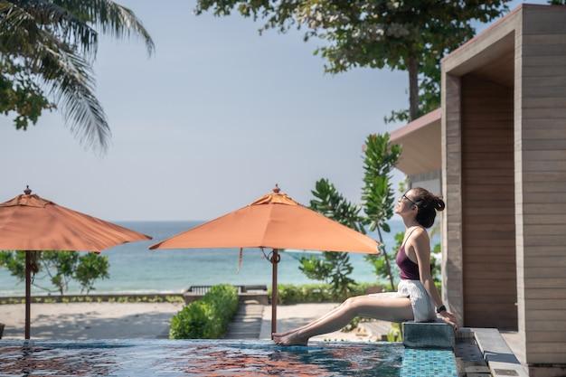 Mulher em traje de banho está postando na piscina ao lado da praia do mar.