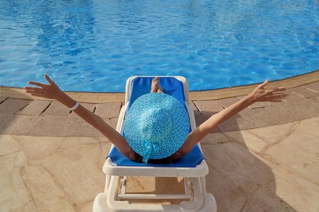 Mulher em traje de banho relaxando em uma espreguiçadeira à beira da piscina no verão ao ar livre