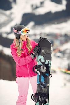 Mulher em traje de snowboard. desportista em uma montanha com uma prancha de snowboard nas mãos no horizonte. conceito em esportes