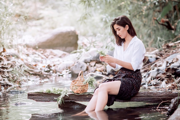 Mulher em traje folclórico lavar legumes para cozinhar