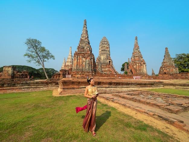 Mulher em traje tradicional tailandês com pagode antigo no templo em ayutthaya, tailândia (wat chai wattanaram), vista panorâmica