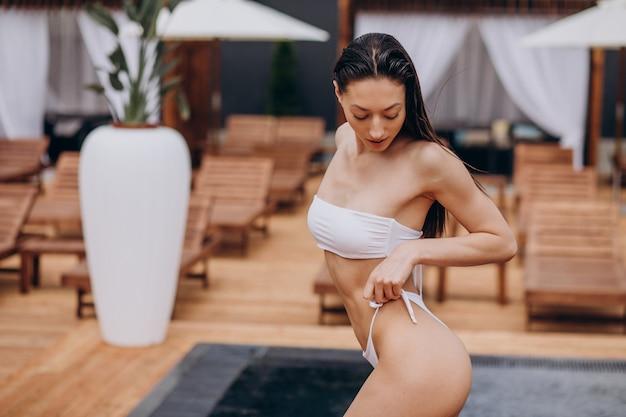 Mulher em trajes de banho à beira da piscina