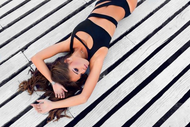 Mulher em trajes de banho elegantes deitada no chão de madeira