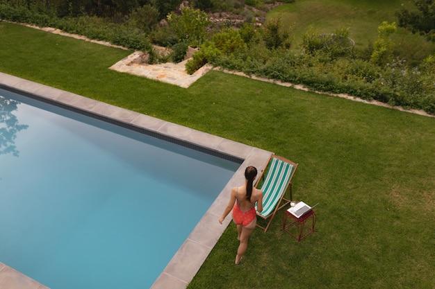 Mulher em trajes de banho perto da piscina no quintal