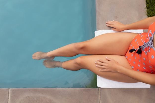 Mulher em trajes de banho relaxante perto da borda da piscina