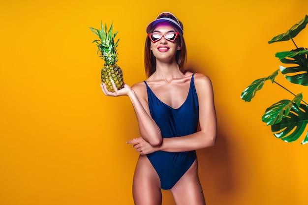 Mulher em trajes de banho segurando abacaxi