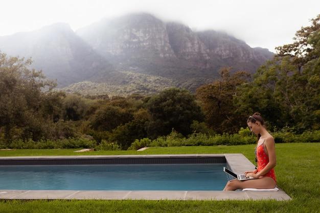 Mulher em trajes de banho usando laptop perto da piscina no quintal