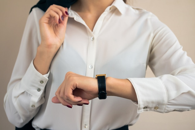 Mulher em trajes de negócios olhando o tempo na mão relógio closeup
