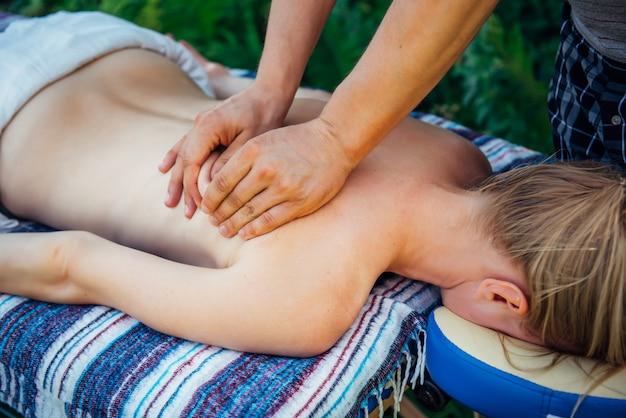 Mulher em tratamentos de massagem no spa ao ar livre, terapia manual, restauração da saúde das costas e coluna vertebral.