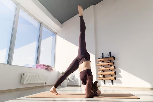 Mulher em um agasalho fica com as mãos em pé durante um treino em um estúdio de ioga