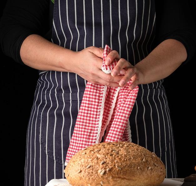 Mulher em um avental listrado azul limpa as mãos com um guardanapo têxtil vermelho depois de fazer pão