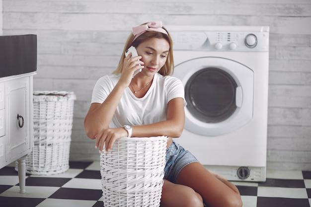 Mulher em um banheiro perto de lavagem mashine