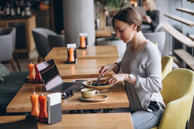 Mulher em um café almoçando e falando no telefone