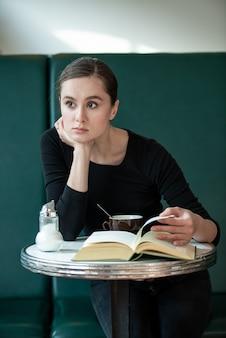 Mulher em um café lendo bebendo café lendo livro em paris