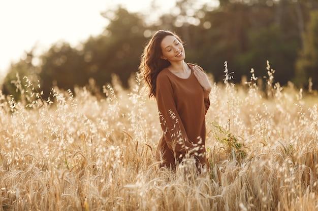 Mulher em um campo de verão. morena com um suéter marrom.