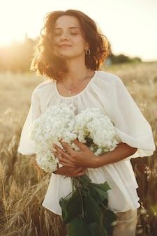 Mulher em um campo de verão. morena em uma camisa branca.
