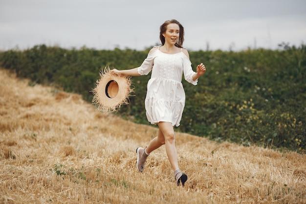 Mulher em um campo de verão. senhora de vestido branco.